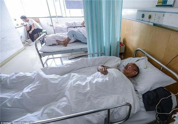 Một người đàn ông được cứu từ vụ sập nhà đang nằm trên giường bệnhở Bệnh viện Trung ương Ôn Châu.
