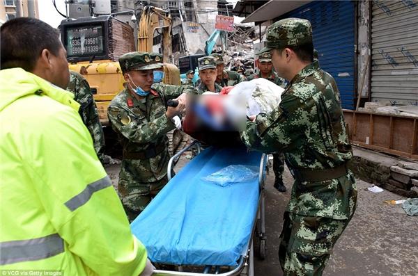 Các nhân viêncứu hộ đưamột người bị thương ra khỏiđống đổ nát của tòa nhà bị sập ở Ôn Châu, Trung Quốc.