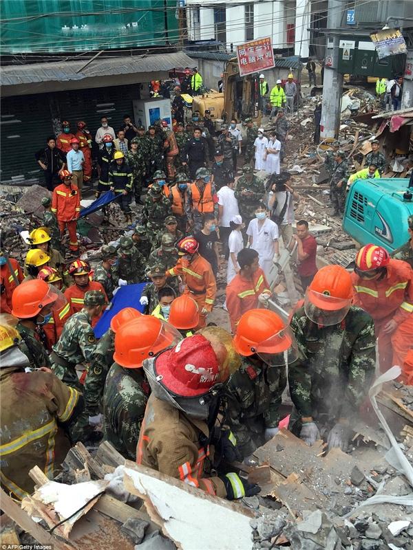 Y tá, nhân viên cứu hộ, nhân viên cứu hỏa, cảnh sát và các cơ quan khác đứngxung quanh hiện trường của cáctòa nhà sụp đổ.