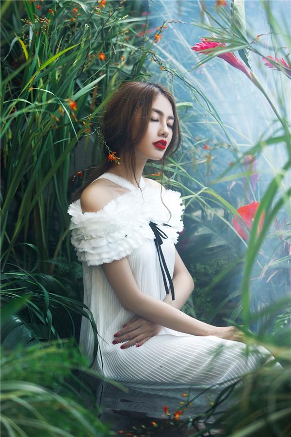 Linh Chi xuất hiện giữa khung cảnh tràn ngập hoa lá tựa như thiên thần trong những thiết kế lấy sắc trắng tinh khôi làm chủ đạo. Nữ người mẫu giấu đường cong trong thiết kế váy suông, trễ vai hợp xu hướng. Tổng thể là sự hòa quyện giữa chi tiết dập li, dún bèo phân tầng điệu đà, ngọt ngào.