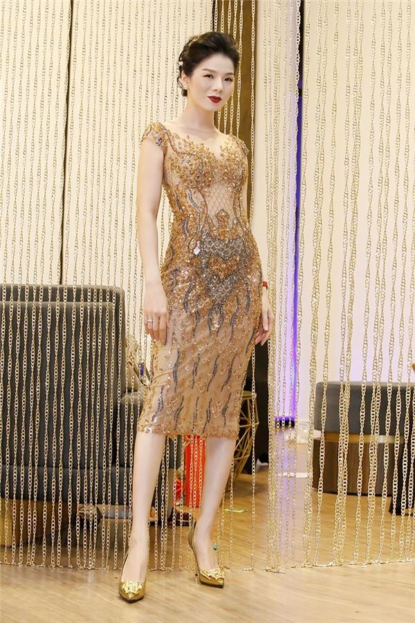 Nữ ca sĩ xuất hiện vô cùng gợi cảm trong dáng váy cocktail xuyên thấu gợi cảm. Thiết kế với sắc vàng ánh kim tôn lên nét sang trọng, quý phái của người mặc.