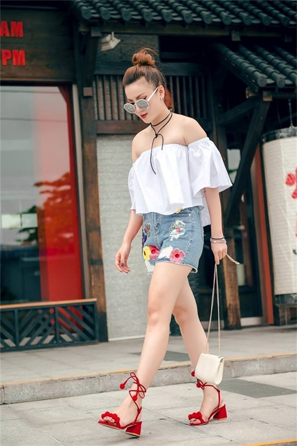 Chiếc quần short denim kết hợp họa tiết thêu với tông màu nổi bật của Yến Nhi làm gợi nhớ đến mốt thời trang những năm 2000. Cô nàng khéo léo kết hợp áo trễ vai, phụ kiện đồng điệu màu sắc với chi tiết.