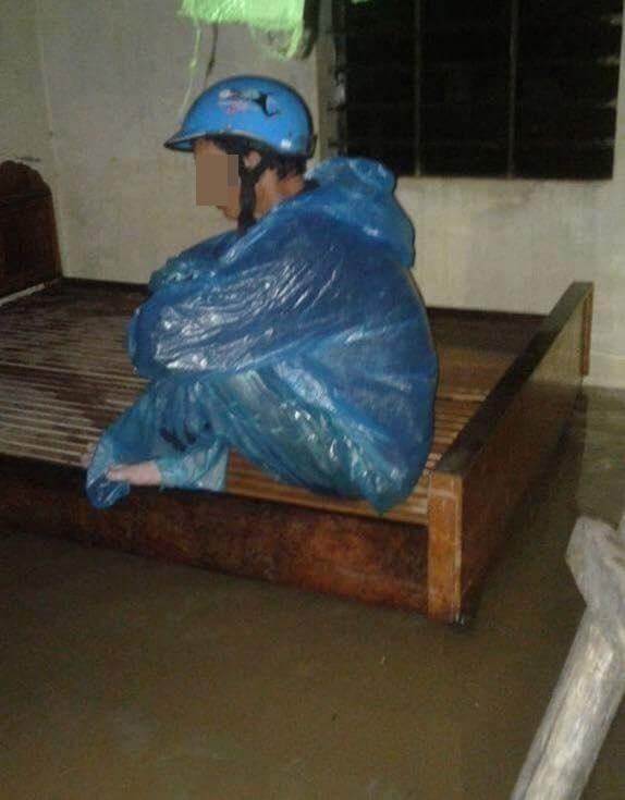 Người đàn ông mệt mỏi sau những giờ oằn mình chống chọi với lũ. Ảnh: facebook Trung Kiên Nguyễn