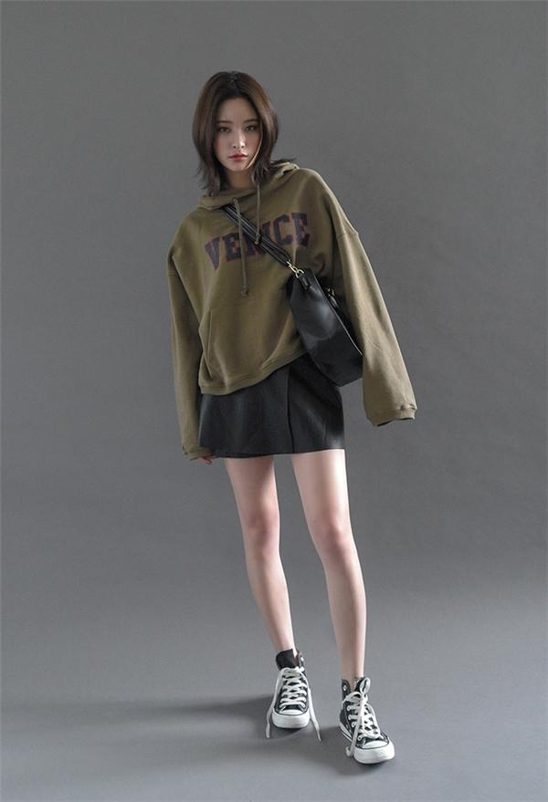 Áo hoodie kết hợp với váy ngắn tạo vẻ ngoài trẻ trung, hiện đại.