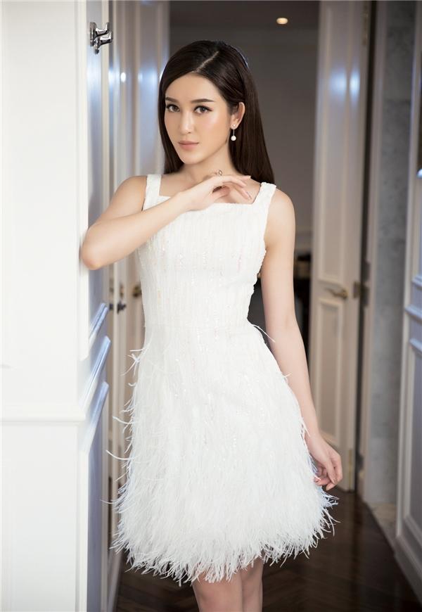 Bộ váy trắng vừa thanh lịch với phần vai to bản, vừa gợi cảm với chiều dài trên gối kết hợp chi tiết lông đính kết mềm mại.