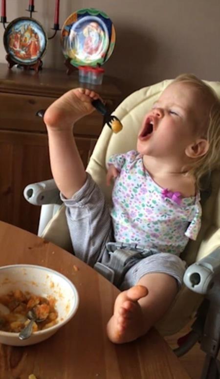 Sau khi được mẹ hướng dẫn, cô bé đã dùng dĩa bằng chân một cách khéo léo.