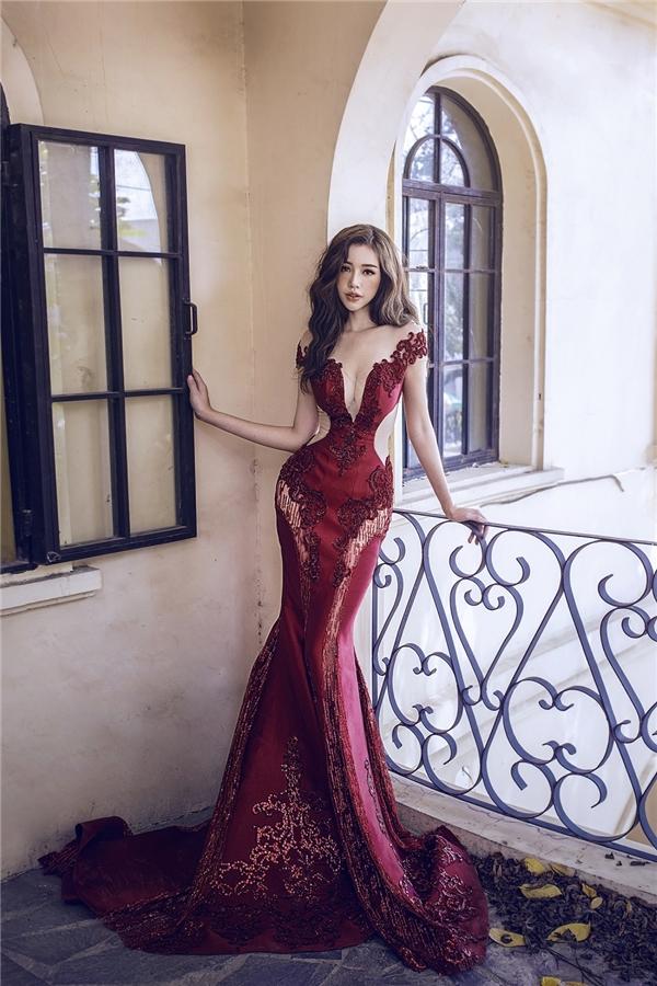 Elly Trần trông vô cùng gợi cảm với phom váy đuôi cá trên nền sắc đỏ rượu sang trọng, quyến rũ. Chiếc váy trông tựa như một bức tranh hoàng gia với loạt họa tiết ren được đính kết kì công, tỉ mỉ. Phần cut-out ở thắt eo càng giúp người mặc trông ấn tượng hơn.