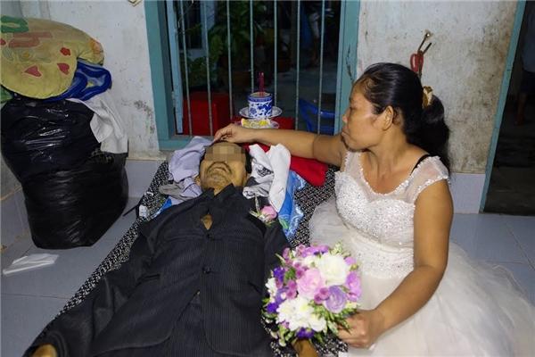 Cô Loan mặc váy cưới trắng, tay cầm hoa cưới, khuôn mặt thấtthần chẳng kịp trang điểm, luôn ngồi bên giường nắm chặt tay chú. (Ảnh: Hung Kim)