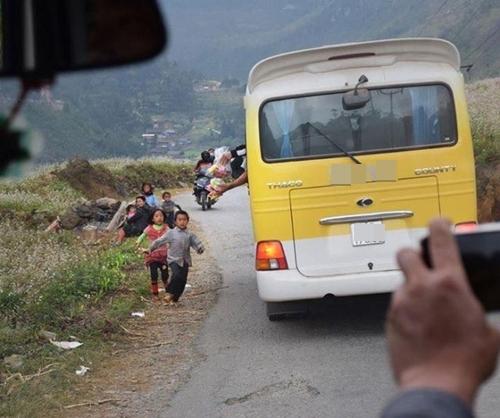 Nhiều trẻ em sẵn sàng bỏ học để chạy theo xe và chờ du khách tặng quà.Ảnh: Chu Đức Hòa.