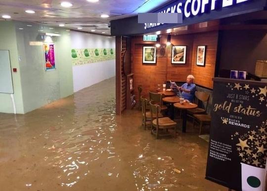Cụ ông Hồng Kông thảnh thơi ngồi cà phê đọc báo bất chấp lũ lụt