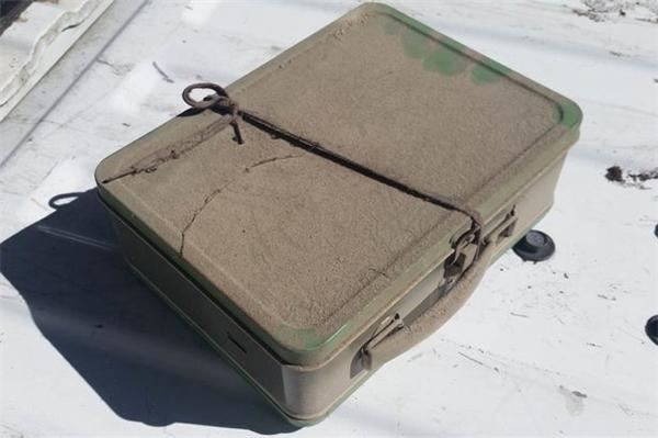 Chiếc vali màu xanh lá bám đầy bụi chứng tỏ đã được giấutại đây từ rất lâu.