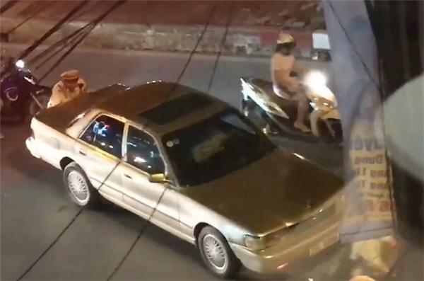 Chiến sĩ CSGT giúp dân đẩy ô tô chết máy giữa phố Hà Nội. (Ảnh cắt từ clip)
