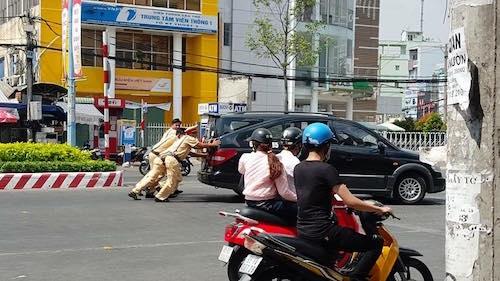 3 chiến sĩ CSGT thuộc Công an quận Ninh Kiều (TP Cần Thơ) đang giúp đỡ người dân đẩy xe dưới trời nắng. (Ảnh: Internet)