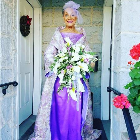 Chiếc váy màu tím, chiếc mạng che mặt màu tím nhạt khiến bà thêm lộng lẫy, quyến rũ.
