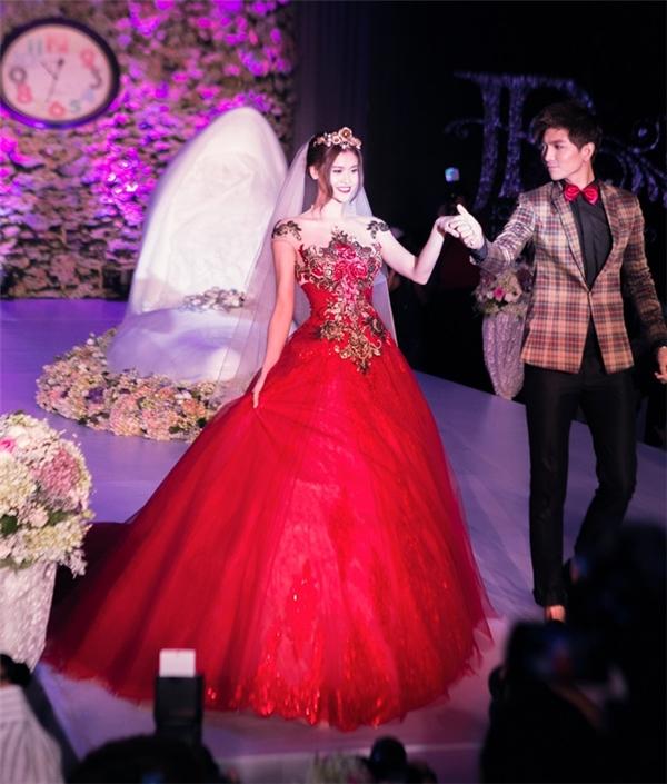 Dù chưa được mặc áo cưới chính thức nhưng Trương Quỳnh Anh cũng đã có dịp sánh đôi cùng Tim tham gia trỉnh diễn chúng. Thiết kế với sắc đỏ rực mang lại vẻ ngoài lộng lẫy, nổi bật cho bà mẹ một con.
