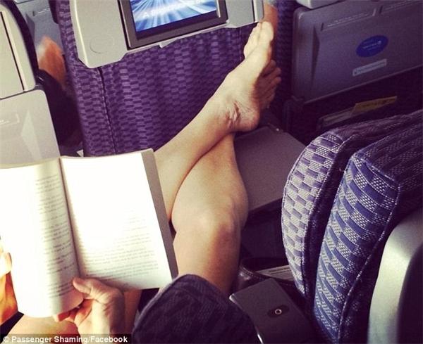 Dùng bàn ăn trên máy bay để chân lên và hồn nhiên đọc sách khiến người khác có cái nhìn ái ngại.