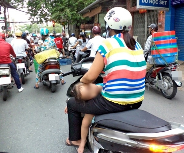 Người mẹ thản nhiên lái xe bằng một tay, tay còn lại ôm con ngủ gật như thế này.