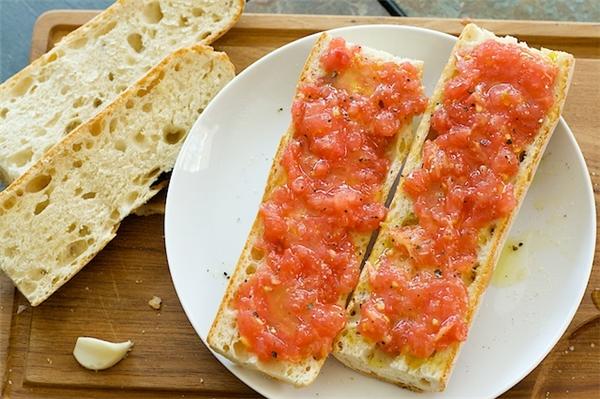 Tây Ban Nha:Bữa sáng nhanh ở Tây Ban Nha là một loại bánh có tên là Pan con Tomate, đơn giản nhưng vô cùng thơm ngon. Phía trên bánh mìnướng là tỏi tươi, cà chua chín, sau đó rẩy muối và dầu olive lên trên. Tiếp đó, pho mát, thịt xông khói xúc xích có thể lại được phủ lên trên.