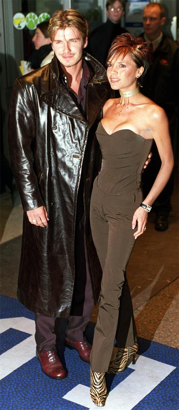Trench coat da bóng lộn giúp cho cậu Beckham tỏa sáng bên cạnh mợ Vic sexy.