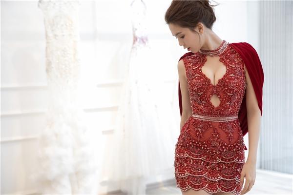 Phần thân váy được tạo nên từ những lớp ren, lưới họa tiết xếp chồng một cách tinh tế. Điểm nhấn nằm ở phần xẻ ngực sâu nhưng chừng mực cùng hàng nghìn viên đá quý được đính kết khắp mặt chất liệu.