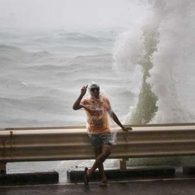 Một du khách tên Tsim Sha Tsui đứng trước Vịnh Victoria để chụp ảnh selfie trong cảnh áo mưa trùm kín người. Ảnh: SCMP