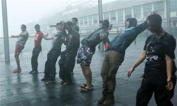 """Nhóm nam thanh niên này đang """"đo tốc độ gió"""" khi cơn bão Haima tràn vào Hồng Kong."""