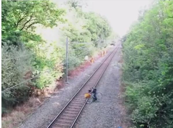 Một người đàn ông đang cố dắt xe đạp qua đường ray. (Ảnh: Cắt clip)