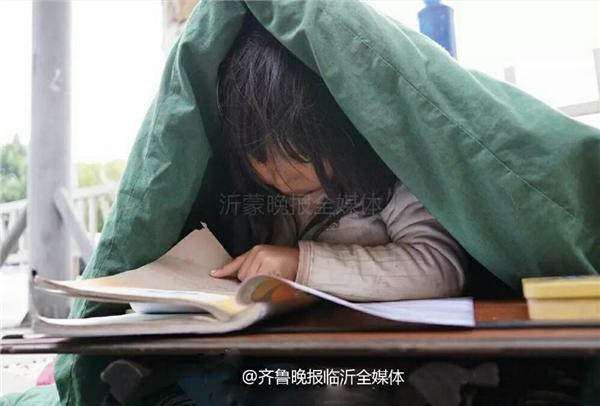Cô bé quấn mình trong chiếc chăn cũ kĩ ngồi co ro chăm chú học bàibên vệ đường.