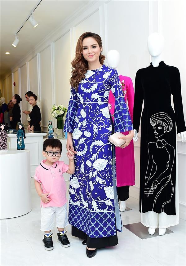 Hoa hậu Diễm Hương đến tham dự sự kiện cùng con trai. Người đẹp trẻ trung với áo dài sắc xanh biếc.