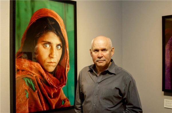"""Nhiếp ảnh gia Steve McCurry bên cạnh bức ảnh """"Cô gái Afghan"""" từng hút hồn cả thế giới. (Ảnh: internet)"""