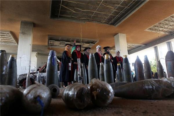 Nhóm sinh viên tạo dáng sau những vỏ đạn cối từng bắn vào tòa nhà chính trong các cuộc đụng độ.