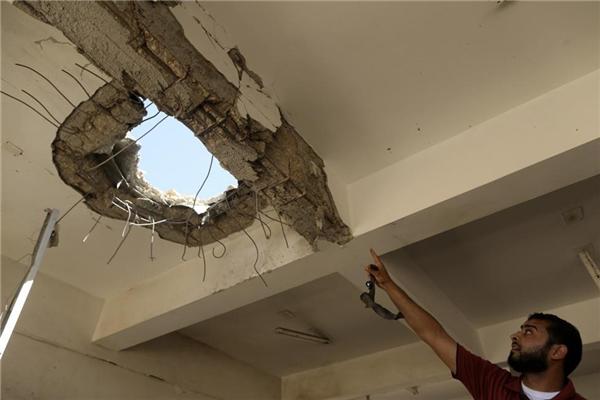 Giảng viên Đại học Benghazi chỉ lên lỗ thủng trên trần nhà sau vụ đánh bom ngày 1/6/2014.