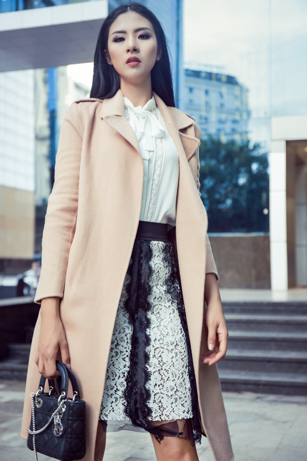 Áo khoác màu be ngọt ngào được Ngọc Hân phối cùng chân váy ren gợi cảm, áo sơ mi thắt nơ cổ điển.