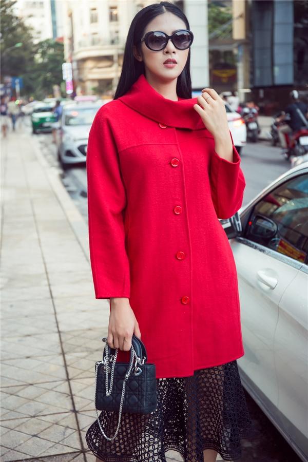Sự gợi cảm của chất liệu ren lưới được tiết chế bằng áo măng tô cổ lọ màu đỏ nổi bật. Ngọc Hân kết hợp trang phục cùng mắt kính, túi Dior đồng điệu màu sắc có giá hàng chục triệu đồng.
