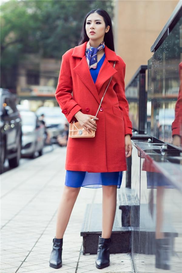 Hoa hậu Việt Nam 2010 không quên lăng xê mốt khăn họa tiết đang thịnh hành khi kết hợp cùng váy xanh, áo khoác đỏ tương phản.