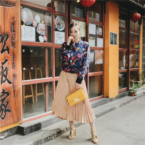 Nữ diễn viên lăng xê áo khoác bomber họa tiết, mốt thời trang đang thịnh hành tại các kinh đô thời trang lớn, đặc biệt tại Seoul Fashion Week vừa qua. Kết hợp cùng chiếc áo khoác cá tính là chân váy xếp li điệu đà với tông ánh kim nổi bật.