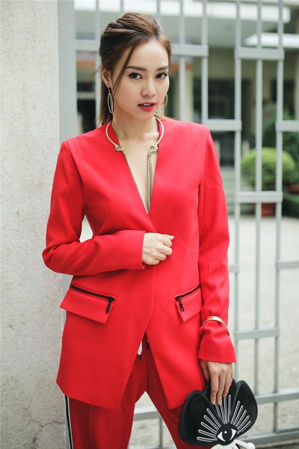 Lan Ngọc nổi bật trên phố với sắc đỏ cùng thiết kế suit cách điệu với chi tiết xẻ ngực, nhấn nhá đối xứng hai bên quần. Tổng thể trông thú vị hơn với chiếc ví cầm tay có hình dáng độc đáo.