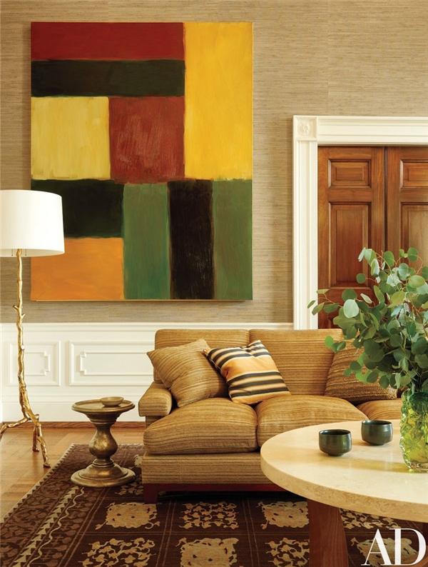 Phòng Thư giãn khá giản dị và ấm cúng với tranh treo tường, chân đèn, bộ ghế bành êm ái và một chiếc bàn gỗ.