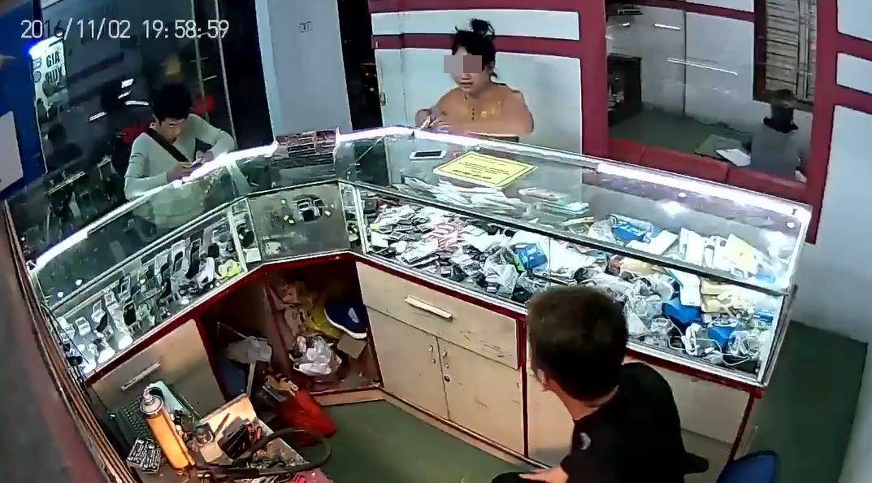 Vị khách nữ bước vào cửa hàng, thảy chiếc điện thoại và pin sạc lên tủ quầy. (Ảnh cắt từ clip)