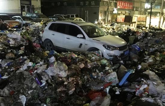 Chiếc xe chìm trong đống rác không thể thoát ra cho đến khi được máy xúc dọn đường.