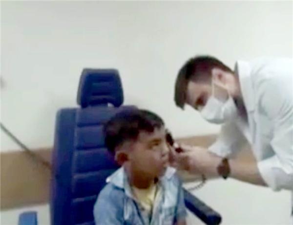 Bác sĩ Cagri dùng kính soi tai để kiểm tra chính xác hơn.