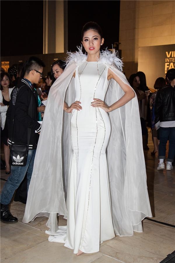 Á hậu Thanh Tú diện cho mình chiếc đầm trắng suôn dài, điểm nhấn là chiếc áo khoác cầu vai đính lông vũ trắng vô cùng kiêu kì.