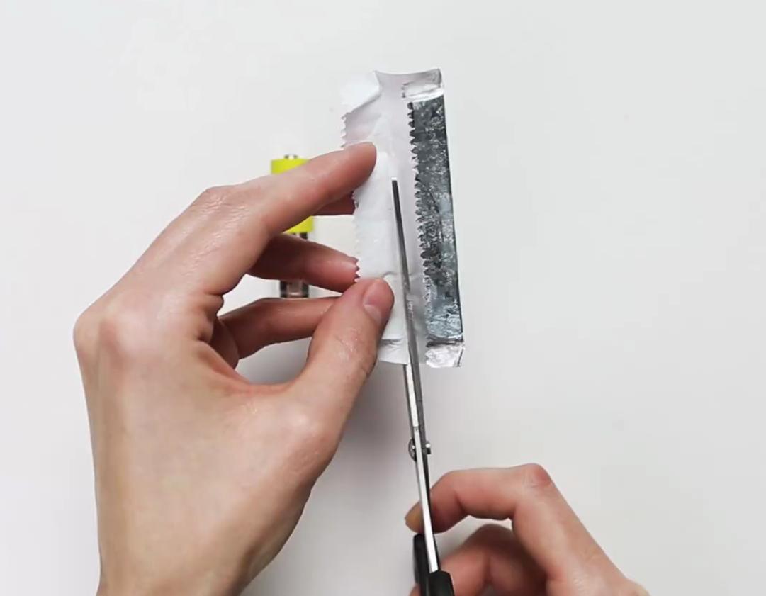 Lấy miếng giấy bạc của thanh kẹo cao su rồi cắt thành một miếng ngắn và nhỏ hơn.