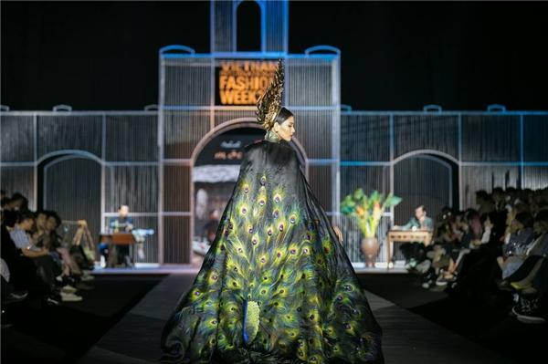 Trương Thị May diện áo dài đen kết hợp áo choàng lộng lẫy chốt show cho nhà thiết kế Đinh Văn Thơ. Cô phải đội chiếc mấn lên đến 10 kg và trình diễn.