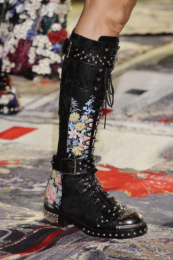 Đôi giày của Alexander McQueen với phần đế bằng sẽ giảm bớt độ chênh vênh khi di chuyển. Ngoài ra thiết kế cũng tạo ấn tượng mạnh bởi những chi tiết kì công, tỉ mỉ. Nhưng độ dài đến tận gối của chúng cũng không khác gì đôi giày neon bên trên của Balenciaga.
