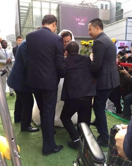 Chú rể quỳ xuống cầu hôn trướcsự chứng kiến của mọi người.