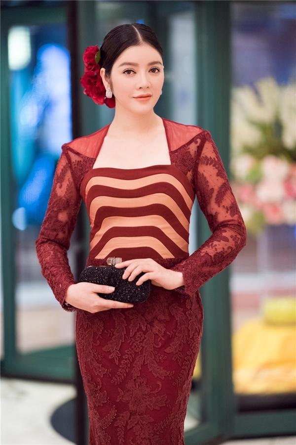 Trên thảm đỏ bế mạc Liên hoan Phim Quốc tế Hà Nội 2016, Lý Nhã Kỳ trở thành tâm điểm khi diện bộ váy ôm sát với tông đỏ rượu sang trọng, quý phái. Thiết kế kết hợp nhiều chất liệu và được tạo điểm nhấn bằng những đường kẻ gợn sóng với hai sắc độ sáng tối đan lồng.