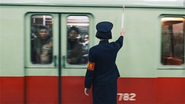 Hình ảnh nữ nhân viên nhà ga đã thổi còi báo hiệu cho người lái tàu biết còn hành khách chưa lên tàu, trong khi cả đoàn tham quan đã lên tàu, thì chiếc cửa tàu bỗng dưng đóng lại.