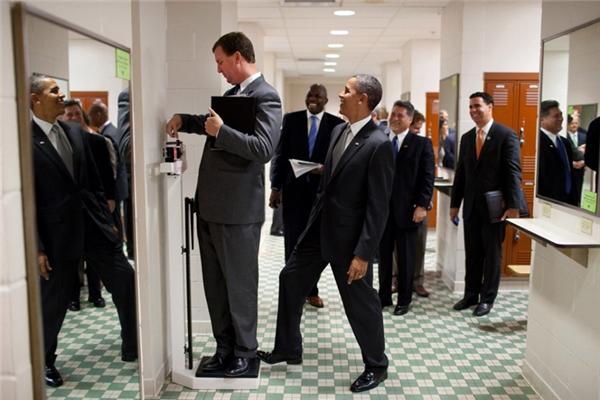 Ông đạp chân lên chiếc cân trong khi Giám đốc Nhà Trắng Marvin Nicholson đang đo thử cân nặng của mình trong phòng thay đồ dành cho các vận động viên bóng chuyền tại Đại học Texas.