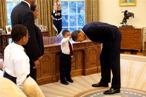 Cúi xuống để cho con trai của một nhân viên Nhà Trắng sờ đầu mình.